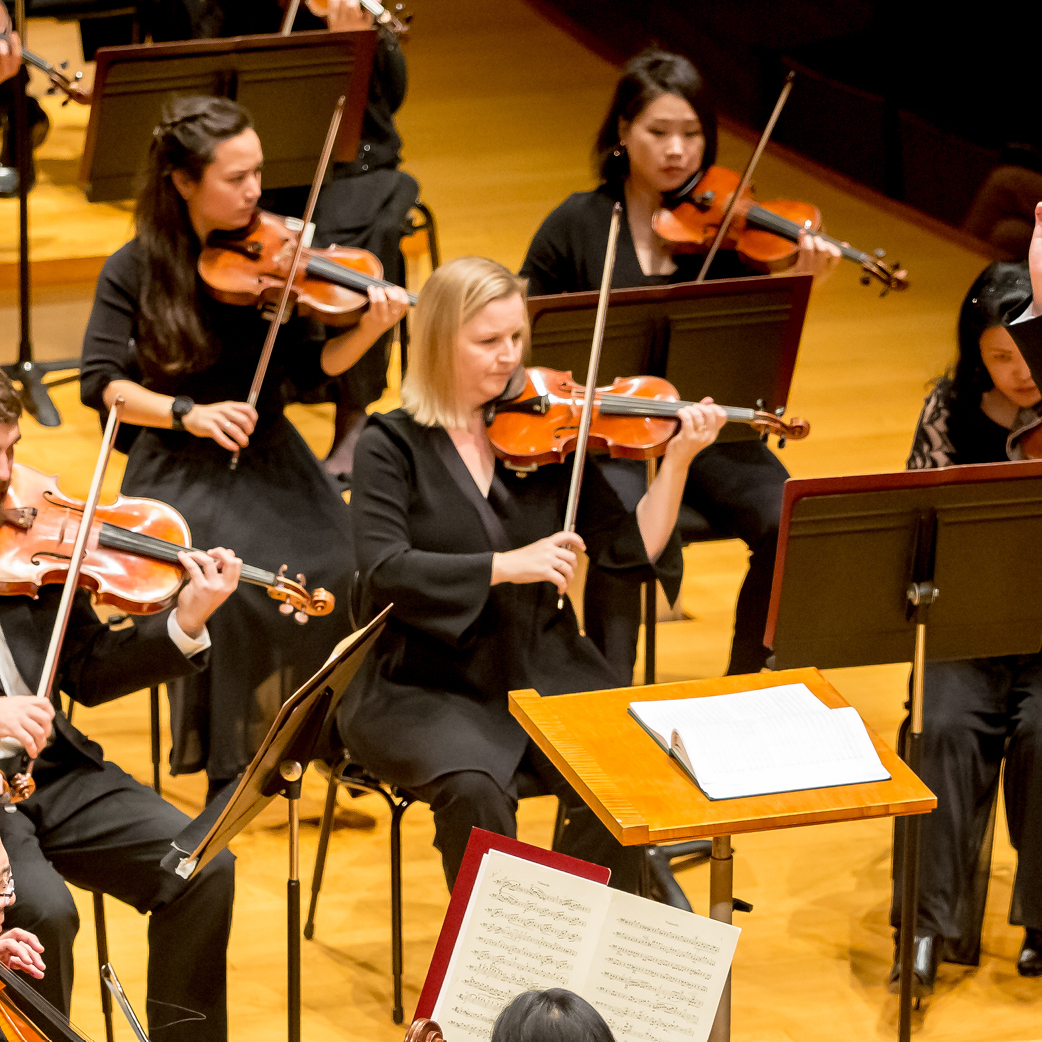 Photo of the Second Violin section of the Kansas City Symphony on stage in Helzberg Hall